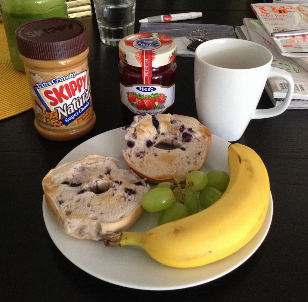 Breakfast of cinnamon raisin bagel with peanut butter and jam and fruits