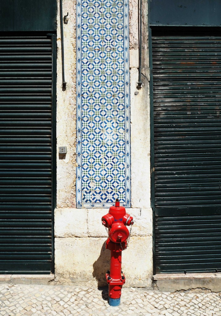 Red fire hydrant in front of azulejos